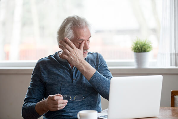 older man at computer with dry eye